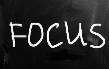 The word Focus handwritten with white chalk on a blackboard