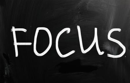 distinctness: The word Focus handwritten with white chalk on a blackboard
