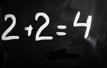 2+2=4 handwritten with white chalk on a blackboard