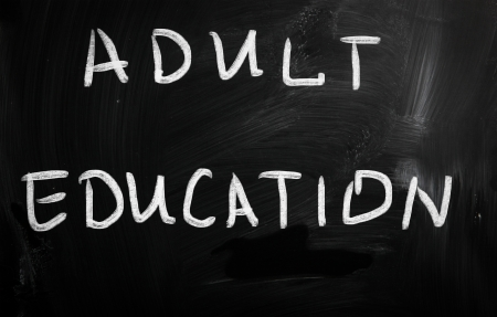 further: Adult Education handwritten with white chalk on a blackboard