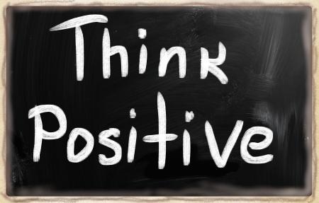 Think positive handwritten with white chalk on a blackboard. photo