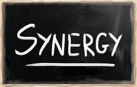 The word Synergy handwritten with white chalk on a blackboard photo