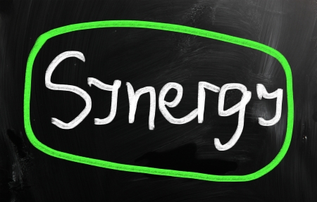 The word Synergy handwritten with white chalk on a blackboard. photo