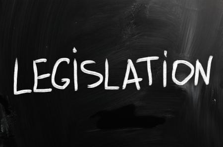 Legislation handwritten with white chalk on a blackboard.