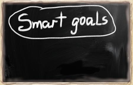 Smart goals handwritten with white chalk on a blackboard.