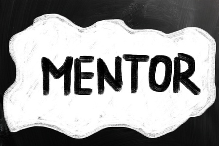 mentor: Mentor handwritten with white chalk on a blackboard. Stock Photo