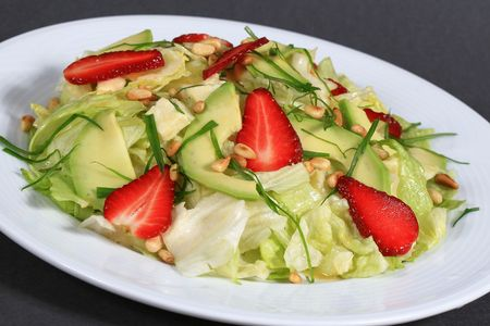 Healthy fruit salad filled with strawberries, apples, topped with peanuts on a bed of mixed spring green salad, close-up