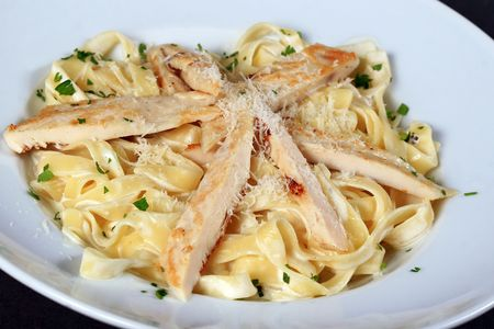 Pasta with chicken pieces in a white bowl