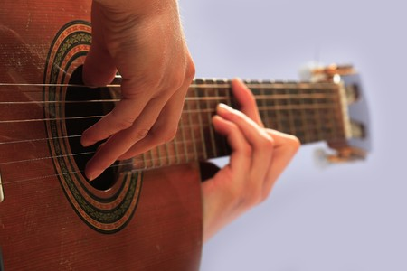 man playing guitar in a gray background