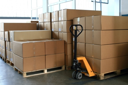 fork pallet truck stacker in warehouse in front of cardboard boxes