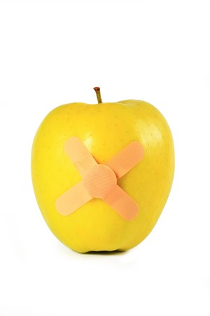 Yellow apple with strapping tape isolated on a white background