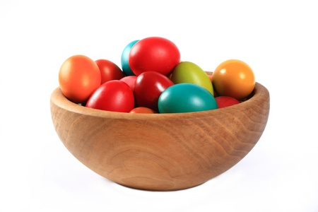 Easter eggs in a wooden bowl on a white background