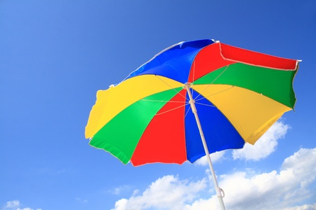 Color striped beach umbrella from the sun against the sky  Stock Photo