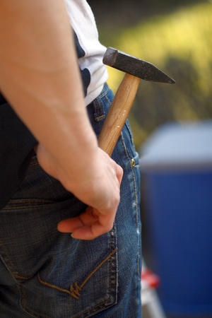 Hand of a worker with a hammer Stock Photo