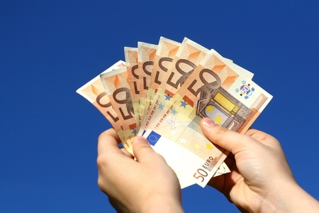 Euro banknotes in woman hand against the sky Stock Photo
