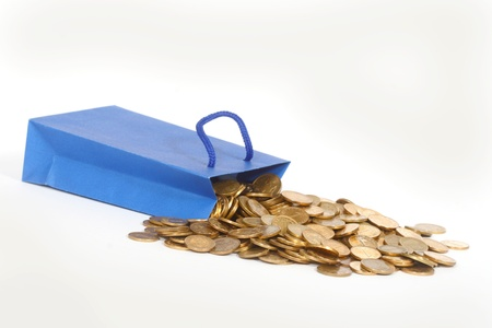 coins and paper gift bag on white background