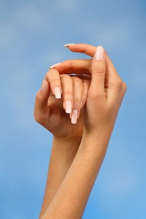 close-ups of the hands of a young woman with long white nails nail against a blue background Stock Photo