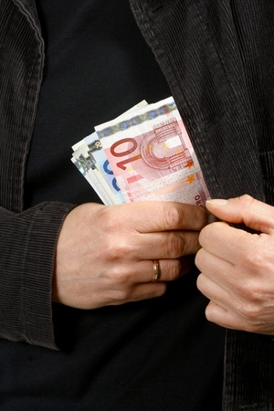 putting money in pocket: A businessman in a black suit putting money in his pocket