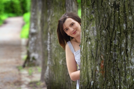 Girl leaning on a tree in the park  Stock Photo