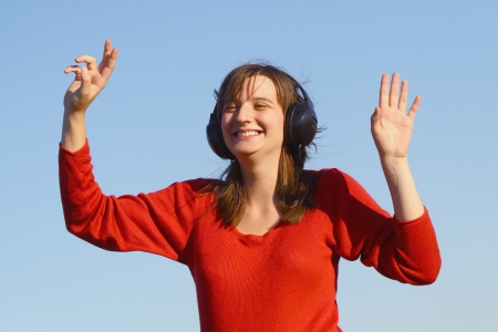 smiling woman listening to music in the background blue sky Stock Photo