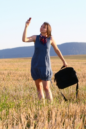 young woman with mobile phone among field