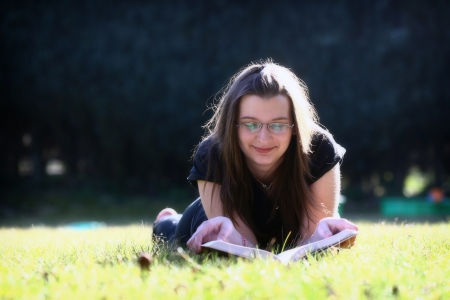 Young woman reading a book on the green grass Stock Photo