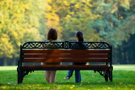 Girls sitting on the bench in the park Stock Photo - 9182218