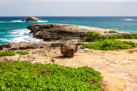 Laie Point State Wayside, peninsula on east coast Oahu, Hawaii, with historical marker on rock.