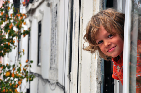 Smiling little boy in the window of the house