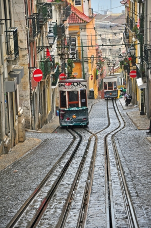 bairro: LISBON, PORTUGAL - DECEMBER 28: Old funiculars goes by the street in Lisbon district Bairro Alto on december 28, 2013. Lisbon transport system has three funiculars routes.