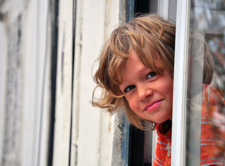 real esate: Smiling boy looking out of window