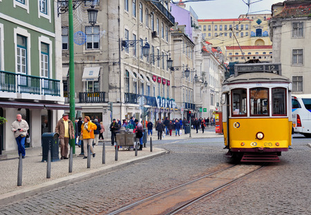 number 12: LISBON, PORTUGAL - NOVEMBER 23: Yellow tram number 12 goes by the street of Lisbon city center on November 23, 2013. Lisbon is a capital and must famous city of Portugal