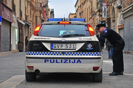 constable: VALLETTA, MALTA - FEBRUARY 28: Car of Malta police department and constable on the street of Valletta on february 28, 2014. Valletta is a capital and the largest city of Malta.