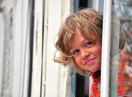 Smiling boy looking out of window