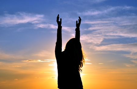 mujer orando: Silueta de la mujer con las manos en el aire Foto de archivo