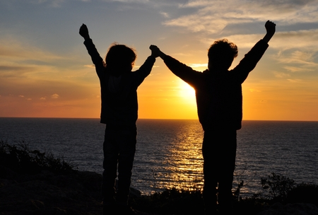 Children holding by hands on sunset photo