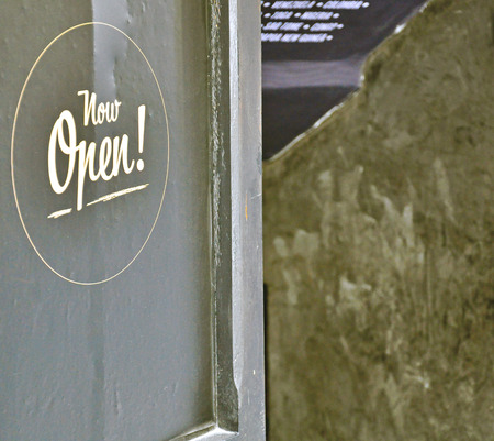 """""""Now Open"""" sign on the black door"""