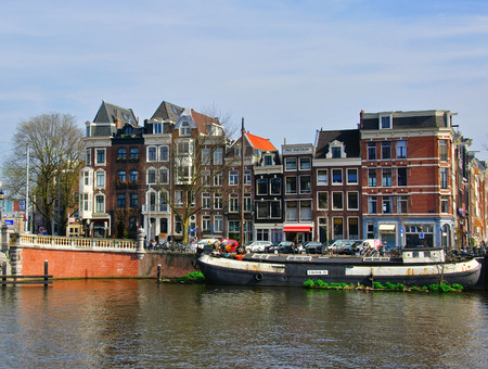 AMSTERDAM, NETHERLANDS - MARCH 27: Houses on the street by the river in Amsterdam on March 27, 2012. Amsterdam is the capital and most populous city of the Netherlands.