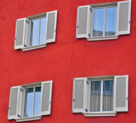 open windows: Open windows on red wall