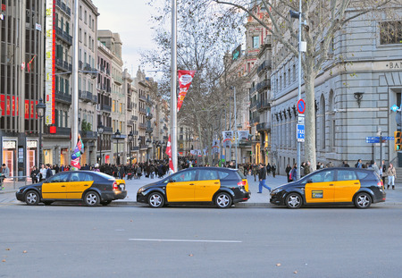 taxi famous building: BARCELONA, SPAIN - JANUARY 29: Taxi cars on the street of Barcelona downtown on January 29, 2015. Barcelona is the second largest city of Spain. Editorial