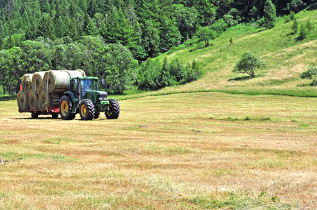 deere: MORGEX, ITALY - JULY 11: Tractor John Deere works in the field in Morgex town on July 11,  2015. John Deere is an American corporation that manufactures agricultural machinery. Editorial
