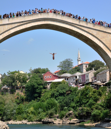 hercegovina: MOSTAR, BOSNIA - AUGUST 10, 2012: Undefined man jumping from the bridge in old town of Mostar, Bosnia on August 10, 2012. Mostar is the most famous touristic city of Bosnia.