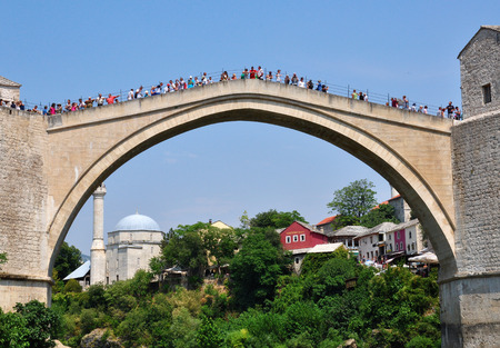 hercegovina: MOSTAR, BOSNIA - AUGUST 10, 2012: Undefined people on the bridge in old town of Mostar, Bosnia on August 10, 2012. Mostar is the most famous touristic city of Bosnia.