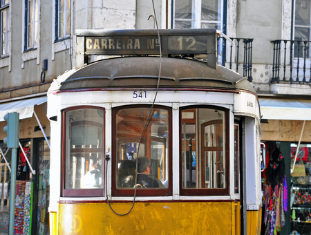 12 13: LISBON, PORTUGAL - NOVEMBER 13: Yellow tram number 12 goes by the street of Lisbon city center on November 13, 2013. Lisbon is a capital and must famous city of Portugal.
