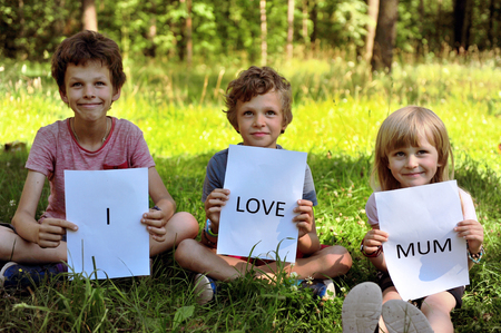 i kids: Three brothers with a sign I love mum Stock Photo