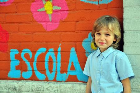 niño sonriendo a la pared en el patio de la escuela