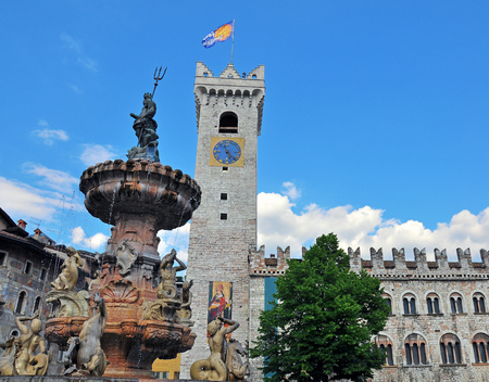 Old tower and fountain sculpture of Trento cathedral square, Italy