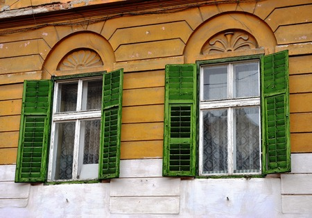 open windows: Open wooden windows with the green blinds on the yellow wall