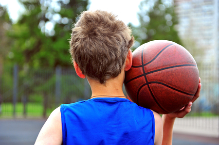 Back view of an young basketball player with a ball