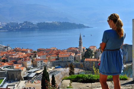 Young woman looking at Budva old town, Montenegro